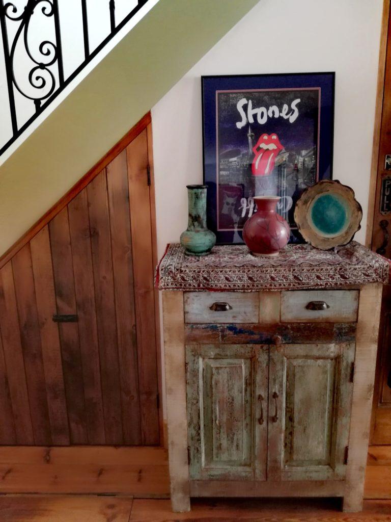 Jedna z komód w salonie, wykonana z indyjskiej łódki i Rolling Stones w tle